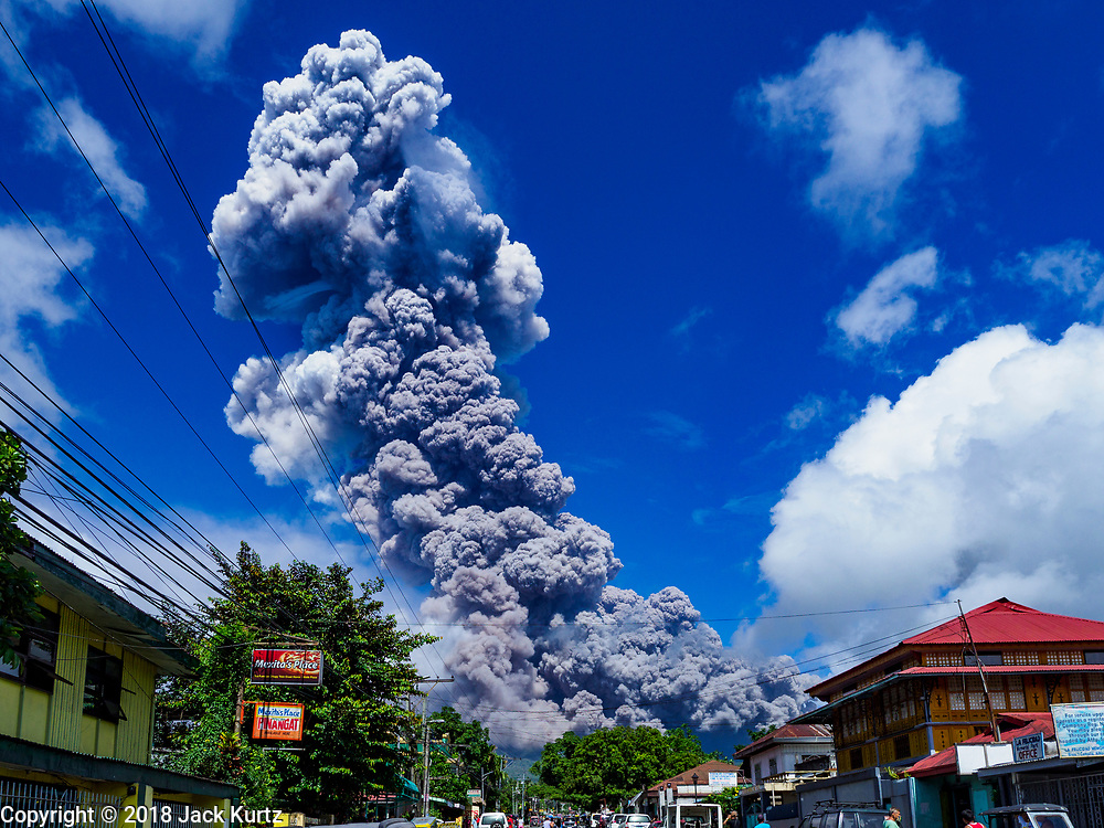 "22 JANUARY 2018 - CAMALIG, ALBAY, PHILIPPINES: An eruption of the Mayon volcano Monday afternoon in Camalig. There were a series of eruptions on the Mayon volcano near Legazpi Monday. The eruptions started Sunday night and continued through the day. At about midday the volcano sent a plume of ash and smoke towering over Camalig, the largest municipality near the volcano. The Philippine Institute of Volcanology and Seismology (PHIVOLCS) extended the six kilometer danger zone to eight kilometers and raised the alert level from three to four. This is the first time the alert level has been at four since 2009. A level four alert means a ""Hazardous Eruption is Imminent"" and there is ""intense unrest"" in the volcano. The Mayon volcano is the most active volcano in the Philippines. Sunday and Monday's eruptions caused ash falls in several communities but there were no known injuries.    PHOTO BY JACK KURTZ"