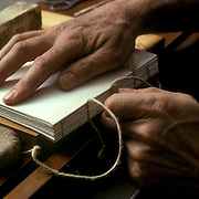 Artist and Fine Art Bookbinder, Gerard Charrier close up of his hands restoring book in his workshop in New York City.