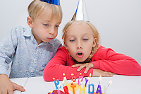 Brother and sister blowing birthday candles at table in house