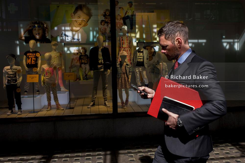 Businessman walks past H&M childrens' clothing window outside central London shop.