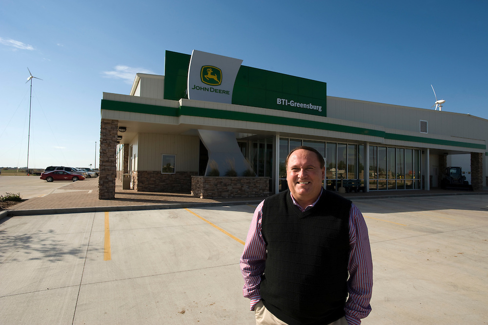 "Greensburg, Kansas, USA..Michael Estes, store manager at BTI-Greensburg John Deere dealership..BTI-Greensburg has built a new John Deere Dealership and Service shop in Greensburg, Kansas. The dealership is designed to be fully daylit using 24 skylights in the service shop and 12 tubular daylighting devices in the retail space. Well insulated metal wall panels - commonly used in refrigerated warehouses - have an assembly R-value of R-16 and eliminate thermal breaks typically seen in metal building construction. The high bay overhead doors include R-14 insulated panels. R-38 roof insulation incorporates thermal blocks to minimize the thermal breaks at the roof structure. A high efficiency 16 SEER VAV provides heating, cooling, and outdoor air to the retail space, combined with CO2 demand controlled ventilation. Hot water is provided with a combination of a waste oil boiler and natural gas boiler. Waste oil from oil changes in the service shop is stored on-site and used during the winter to offset natural gas use. Radiant slab heating minimizes heat loss during the frequent bay door open and close cycles. Two wind turbines (4.2 kW and 1.9 kw) provide electricity to the facility, offsetting an estimated 8% of the building load. The metal building has been certified LEED Platinum at approximatly 50% energy cost savings...""Greensburg: Better, Stronger, Greener!"".On May 4, 2007, an EF5 tornado cut a 1.7-mile path of destruction through Greensburg, Kansas. Winds reaching speeds of 205 miles per hour uprooted trees, demolished homes and leveled the town. Eleven people died and 95% of the buildings were destroyed beyond repair. Residents have since worked furiously to rebuild it in a way that is both economically and environmentally sustainable and to meet the highest environmental standards. Greensburg, whose population has dropped from about 1400 to 800 following the storm and is now growing again, is currently the greenest town in America and the first in the United States"