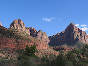 Photograph of a red rock mountain standing tall with blue sky in the distance in Zion National Park on June 12, 2005 in Springdale, Utah. ©Paul Anthony Spinelli
