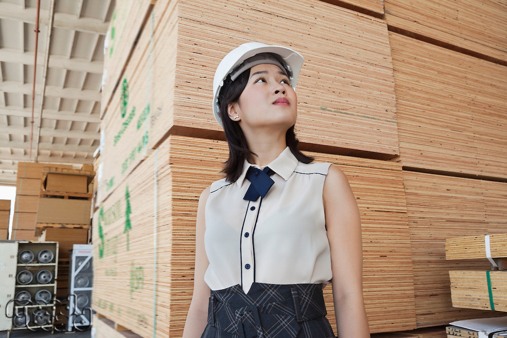 Young female industrial worker looking away with stacked wooden planks in background