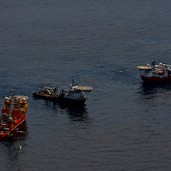 Vessels pass through oil on the surface of the water around the near the site of the Deepwater Horizon oil spill in the Gulf of Mexico near the coast of Louisiana, U.S., on Wednesday, June 2, 2010. BP Plc has given up trying to plug its leaking well in the Gulf of Mexico any sooner than August, laying out a series of steps to pipe the oil to the surface and ship it ashore for refining, said Thad Allen, the U.S. government's national commander for the incident. Photographer: Derick E. Hingle
