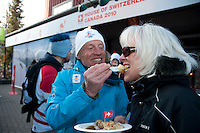 Marcel and Joan Richoz, Whistler locals, enjoy raclette outside the House of Switzerland during the 2010 Olympic Winter Games in Whistler, BC Canada.
