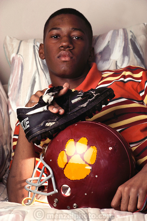 """Toy """"Troy"""" Trice (15 years old) was hit by lightning during high school football practice in September of 1991. The strike tore a hole in his helmet, burned his jersey and blew his shoes off. He recovered from a two day coma with burns and memory loss. Trice at home with the equipment he was wearing when hit. MODEL RELEASED (1993)"""