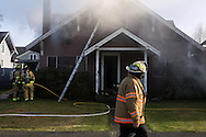 (Gabe Green   The Daily World)<br /> <br /> Hoquiam fire chief Paul Dean walks by a smoking house on Third street in Hoquiam Tuesday as firefighters work to contain the last of the fire which started early in the afternoon.
