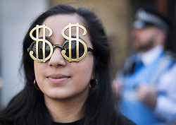 © Licensed to London News Pictures. 12/05/2016. London, UK. A demonstrator wears dollar sign sunglasses as she protests about corruption outside the anti- corruption summit. Prime Minister David Cameron is hosting a one day summit which is addressing world corruption. Photo credit: Peter Macdiarmid/LNP
