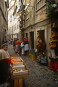 Fruit and buyers in the narrow streets of the Bairro Alto district - or Upper City - the oldest of Lisbon's residential quarters. A local woman across the narrow, high-sided street, yawns while an orange and apple seller looks for her next customer on the cobbled lane. <br /> Lisbon's Bairro Alto quarter is located above Baixa and developed in the 16th Century. Suffering very little damage in the earthquake of 1755, it remains the area of most character and renowned for its residential and working quarter for craftsmen and shopkeepers. At night, life takes on a different personality when bars and up until the 60s, prostitution gave the district a bad reputation in the past but nowadays tourists and the chic frequent its streets and traditional 'Fado' (classical Portuguese opera) bars.