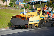 new tarmac being laid by a road laying machine in Auckland, New Zealand