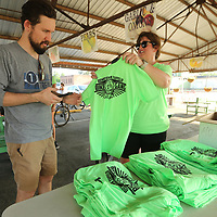 Matthew Knight of Tupelo, receives his Downtown Tupelo Bike Gang T-shirt from Meredith Martin at the Farmers Depot Wednesday night. The Downtown Tupelo Bike Gang made it debut bike ride around downtown Tupelo on Wednesday night.