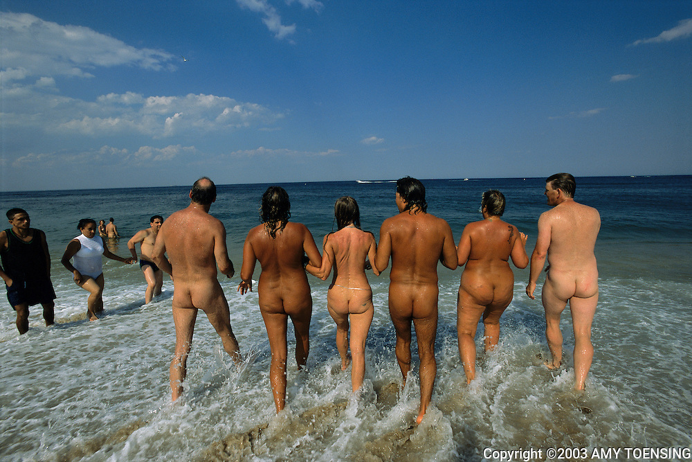 SANDY HOOK, NJ - JULY 12: Friends skinny-dip together, July 12, 2003 in the ocean off Gunnison Beach, Sandy Hook in Gateway National Recreational Area, New Jersey. Gunnison has been a destination for nudists since the 1970s, and many of its visitors have been enjoying the sun and socializing there since its beginning. The Jersey Shore, a 127 mile stretch of coastline known for its variety of beaches, boardwalks, small towns, natural beauty and summer crowds, has been a popular summer destination for over a century. (Photo By Amy Toensing)