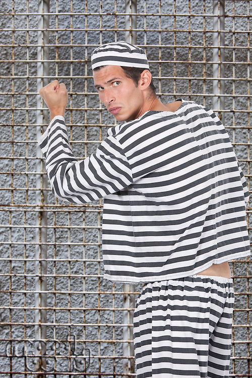 Portrait of young male prisoner in uniform standing against prison cell