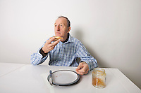 Senior man eating bread spread with sweet jelly jam at table