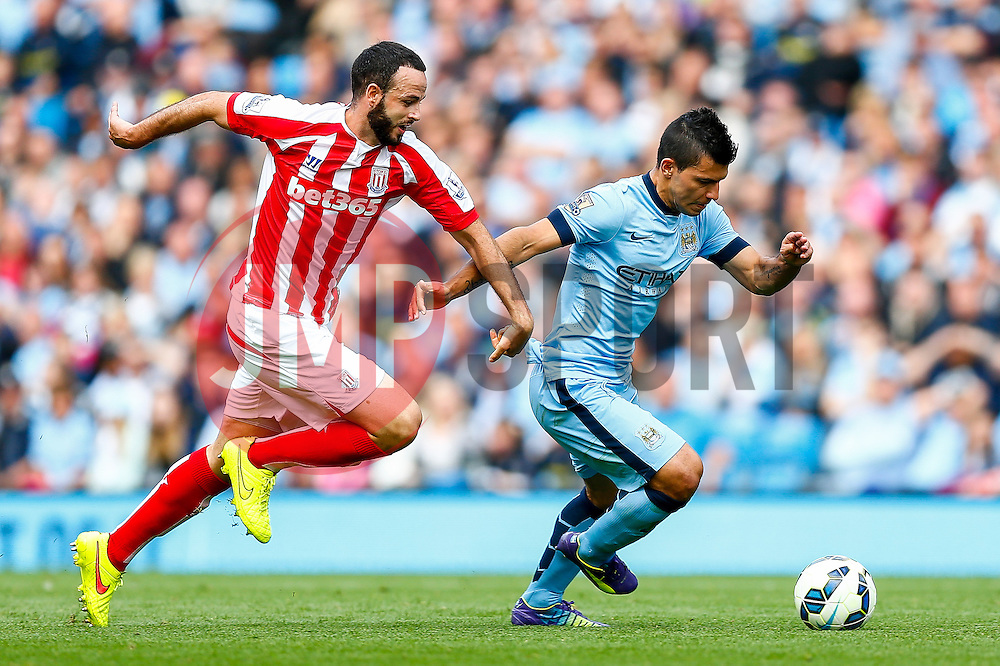 Sergio Aguero of Manchester City is challenged by Marc Wilson of Stoke - Photo mandatory by-line: Rogan Thomson/JMP - 07966 386802 - 30/08/2014 - SPORT - FOOTBALL - Manchester, England - Etihad Stadium - Manchester City v Stoke City - Barclays Premier League.