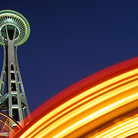 USA, Washington, Seattle, Spinning lights of amusement park rides swirl beneath Space Needle on summer evening