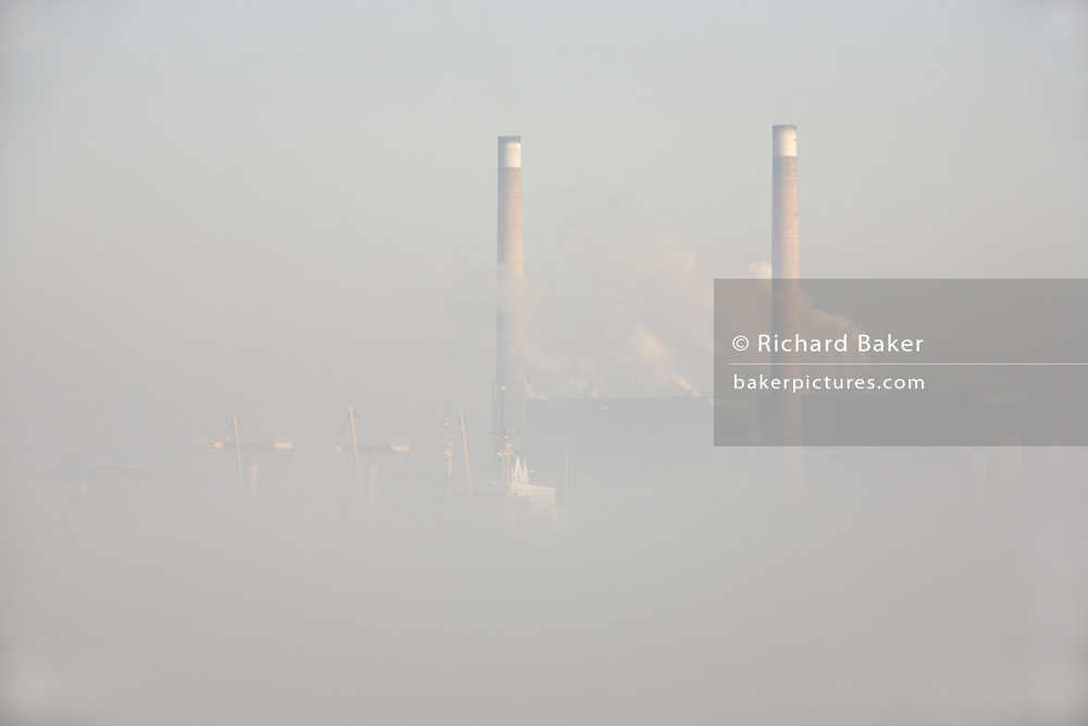 As winter fog lifts, the waters of the River Thames clear to reveal an eerie landscape of industrial river life and architecture at Gravesend, Kent England. It is late-morning and in the hazy distance on the northern river bank, steam clouds near the double twin chimneys of npower's 1400MW coal fired Tilbury power station (powering 1.4 million homes using ?biomass? fuels and low-sulphur coal) which rise above the passing ghostly bulk of a cargo freighter on its last miles of its voyage from open sea into the Thames Estuary and on to Tilbury Docks. Historically, the Thames has long been a route for shipping that kept the capital supplied and although the docks have seen huge decreases in traffic and volume since the second world war, Tilbury remains a busy hub for containerized vessels arrivng from all over the world.