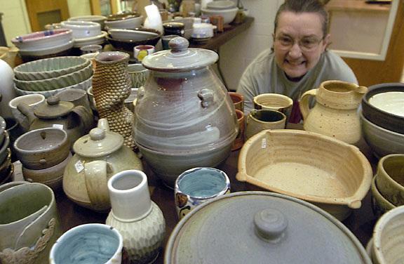 """16194Siegfried Hall Pottery Sale..Betty Reese, a pottery student, looks at pottery at the siegfried hall pottery sale. """"I like to indulge,"""" she said..Johnny Hanson Photo"""