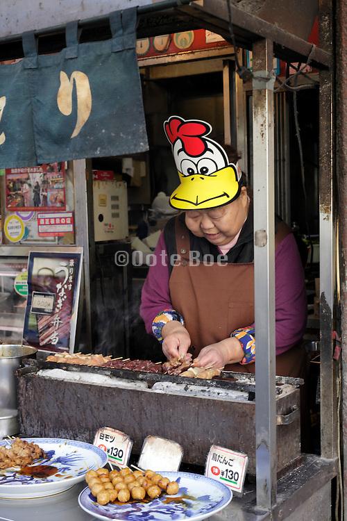 female street food seller preparing Mitarashi-dango Tokyo Japan