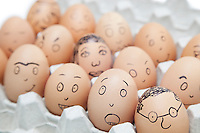 Various facial expressions painted on brown eggs in egg carton