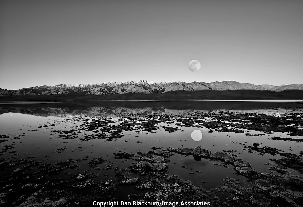 Full moon setting over Telescope Peak in the Panamint Mountains of California and Reflected in Badwater, the lowest point in Death Valley National Park, Black&White.