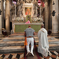 """VENICE, ITALY - SEPTEMBER 02:  Monsignor Lucio Ciglia and one of the """"Regatanti"""" (rowers) pray in Santa Maria della Salute church ahead of Sunday Historic Regata on September 2, 2010 in Venice, Italy. The Historic Regata is the most exciting boat race on the Gran Canal for the locals and one of the most spectacular ***Agreed Fee's Apply To All Image Use***.Marco Secchi /Xianpix. tel +44 (0) 207 1939846. e-mail ms@msecchi.com .www.marcosecchi.com"""
