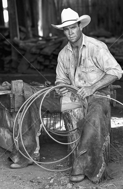 Good looking All American Cowboy wearing chaps,  sitting in barn holding a lasso