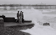 Three friends watching waves on Brighton Beach, UK, 1985
