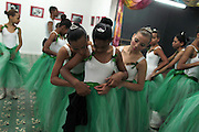Girls fit their ballet skirts during their ballet class at the 'Ballet Santa Teresa' academy in Rio de Janeiro August 13, 2012. 'Ballet Santa Teresa', a non-governmental organization (NGO) gives children who live in areas with social risk, some suffering domestic violence, free ballet classes and other activities as a part of socio-cultural integration project.  Photo by: Pilar Olivares