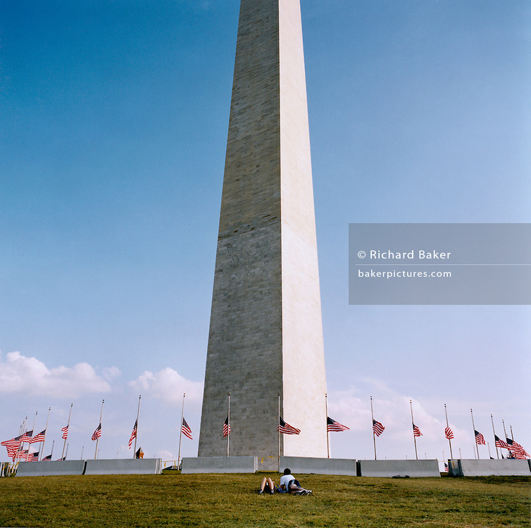 Washington Memorial, Washington DC. Patriotic Americana - After 9/11.American flags fly at half-mast at the Washington memorial, Washington DC. In the week after the September 11th attacks, America sought to express their anger and patriotic unity. Flags fly at half-mast beneath the Washington Memorial, Washington DC...