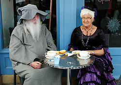 © Licensed to London News Pictures. <br /> 01/11/2014. <br /> <br /> Whitby, Yorkshire, United Kingdom<br /> <br /> A couple dressed for the 20th anniversary of Whitby Goth Weekend sit outside a pavement cafe.<br /> <br /> The event this weekend brings together thousands of extravagantly dressed followers of Victoriana, Steampunk, Cybergoth and Romanticism who all visit the town to take part in celebrating Gothic culture. This weekend marks the 20th anniversary since the event was started by local woman Jo Hampshire.<br /> <br /> Photo credit : Ian Forsyth/LNP