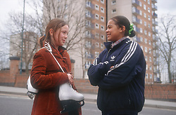 Two teenage girls standing in street talking; one holding ice skates,