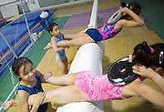 Chinese girls lift weights during an afternoon training session of the Beijing Gymnastic team.