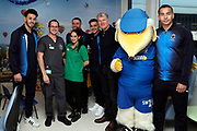 AFC Wimbledon defender Will Nightingale (5), AFC Wimbledon defender Rod McDonald (26), AFC Wimbledon first team coach Glyn Hodges, AFC Wimbledon midfielder Anthony Hartigan (8), AFC Wimbledon attacker Egli Kaja (21), Haydon the Womble delivering Christmas presents to the children on behalf of AFC Wimbledon, at St George's Hospital, Tooting, United Kingdom on 13 December 2018.
