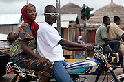 Man, his wife and their child on a motorbike in Tamale, northern Ghana, on Sunday June 3, 2007.