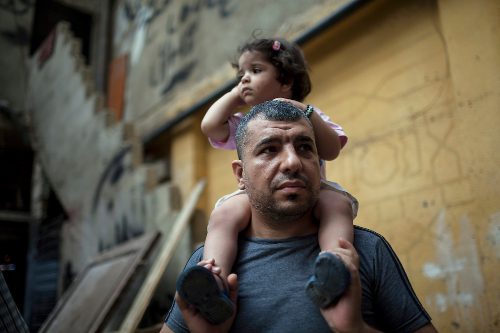 30/06/2013 Shatila refugee camp, Beirut: A Syrian refugee father and daughter live in Shatila refugee camp after fleeing a suburb of Damascus. They brought nothing with them. Shatila is among the oldest of the Palestinian camps established after 1948 in Lebanon, and one of the poorest. Since 2011, housing costs have quadrupled for people fleeing the conflict in Syria, and work is scarce or extremely low-paying. Estimates have placed the number of Syrian refugees in Lebanon at well over 500,000 people.