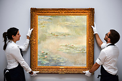 "© Licensed to London News Pictures. 14/06/2019. LONDON, UK. Technicians present ""Nymphéas"", 1908, by Claude Monet (Est. £25-30m). Preview of Impressionist and Modern art sales, which will take place at Sotheby's New Bond Street on 18 and 19 June 2019.  Photo credit: Stephen Chung/LNP"