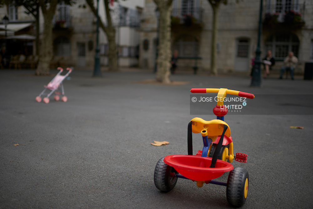 Tricycle  and baby buggy toys on the street in Saint Jean de Luz, France