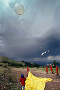 Launching weather balloon with field mills into an approaching electrical lightning storm. Langmuir Atmospheric Research Lab on Mt. Baldy, New Mexico (1992) Lightning occurs when a large electrical charge builds up in a cloud, probably due to the friction of water and ice particles. The charge induces an opposite charge on the ground, and a few leader electrons travel to the ground. When one makes contact, there is a huge backflow of energy up the path of the electron. This produces a bright flash of light, and temperatures of up to 30,000 degrees Celsius.