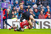George Taylor (#12) of Edinburgh Rugby offloads the ball as he is tackled by Benito Masilevu (#11) of SU Agen Rugby during the European Rugby Challenge Cup match between Edinburgh Rugby and SU Agen at BT Murrayfield, Edinburgh, Scotland on 18 January 2020.