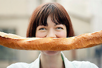 Woman Holding Baguette in Front of Face head and shoulders