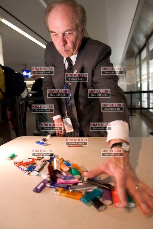 Dennis Homer, assistant federal security director for the San Francisco International Airport, displays numerous confiscated lighters on a table at an airport security check point,  Starting Thursday,  April 14, 2005, air travelers will have to leave their lighters at home. Unlike guns, knives and other dangerous items that a passenger cannot carry aboard but may stow in checked bags, lighters are banned everywhere on a plane.   Photo by Kim Kulish.