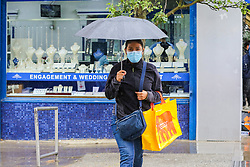 © Licensed to London News Pictures. 27/06/2020. London, UK. A woman wearing a face covering shelters from rain underneath an umbrella in north London following a very hot week which saw highest temperature of the year so far. Photo credit: Dinendra Haria/LNP