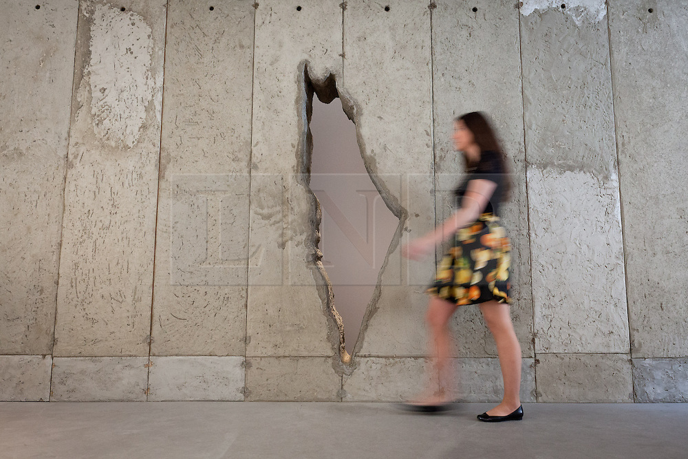 © Licensed to London News Pictures. 20/06/2013. London, UK. An Ayyam Gallery employee walks past an installation by Palestinian artist Khaled Jarrar at the press view for a new exhibition at the gallery in London today (20/06/2013). The exhibition, entitled 'Whole in the Wall', uses cement taken by Khaled from the 700km long apartheid wall that separates the West Bank from the State of Israel. Photo credit: Matt Cetti-Roberts/LNP