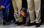 Destiny Auzenne, 9 of Oakland Ca, squeezes through the legs of adults to get a photograph of Governor Schwarzenegger walking to a news conference at the State Capitol.