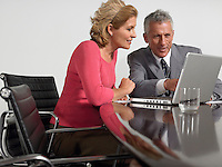Business colleagues using laptop at conference table