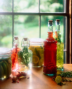 A small selection of several bottles and jars filled with herbs and liquid sit on a windowsill with bright sunlight streaming in