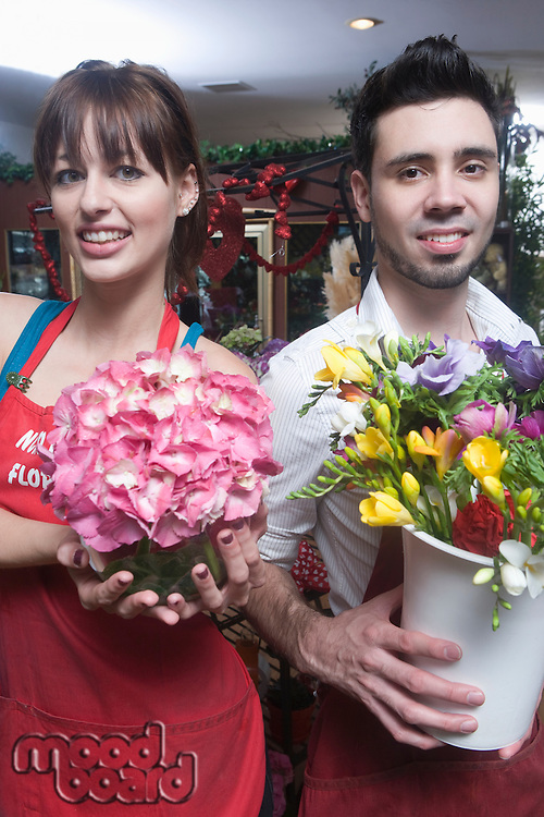 Florists stand holding a bucket of cut flowers and a hydrangea