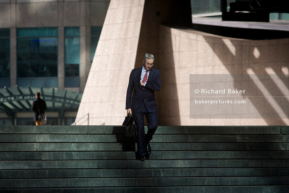 Businessman walking through the Broadgate corporate offices development in the City of London. Walking down steps on his way to or from an appointment or meeting, the man checks an inside pocket as he makes his way into an area of reflected sunlight with the backdrop of the Broadgate development within the ancient boundary of the capital's Square Mile, it's financial district founded by the Romans in AD43.