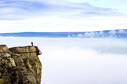 © Licensed to London News Pictures. 31/03/2016. Ilkley UK. Picture shows a walker standing on the Cow & Calf rocks 1,395ft above the fog covered town of Ilkley this morning in Yorkshire. Photo credit: Andrew McCaren/LNP